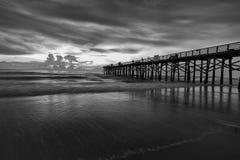 Fine art B&W of Florida coast at dawn. A B&W image of sunrise over the Atlantic Ocean at the pier in Flagler Beach, Florida Stock Photos