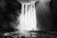 Woman practicing yoga at the Skogafoss waterfall