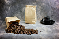 Fine art coffee beans bag and cup. Fine art image of coffee showing a bag of whole beans, a closed bag of coffee and a black espresso cup on a saucer against a Royalty Free Stock Photo