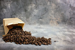 Fine art coffee beans spilling from bag. Fine art image of coffee showing a bag of whole beans, a closed bag of coffee and a black espresso cup on a saucer Royalty Free Stock Photo