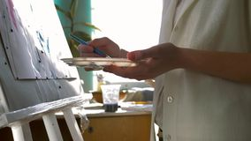 Fine art, happy artist female with inspiration relish paints painting with bright colors on white canvas on easel at. Workroom against sunlit window, shooting stock video