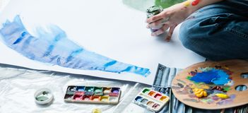 Fine art hobby artist watercolor acrylic paint. Fine art hobby. Cropped shot of artist sitting on floor, creating artwork using watercolor and acrylic paint royalty free stock image