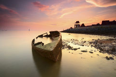 Fine Art image of stranded ship with pieces of ship part silhouette and vibrant sunset sky Stock Images