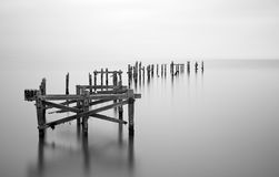 Fine art landscape image of derelict pier in milky long exposure Royalty Free Stock Image