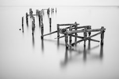 Fine art landscape image of derelict pier in milky long exposure Royalty Free Stock Photography