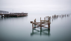 Fine art landscape image of derelict pier in milky long exposure Royalty Free Stock Photos