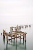 Fine art landscape image of derelict pier in milky long exposure Royalty Free Stock Photo