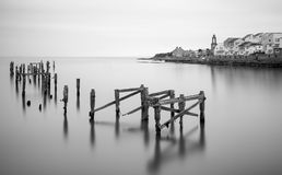 Fine art landscape image of derelict pier in milky long exposure Stock Image