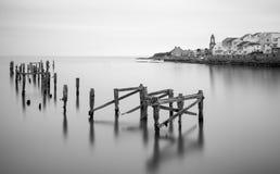 Fine art landscape image of derelict pier in milky long exposure Stock Image