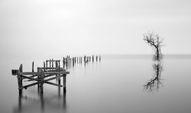 Fine art landscape image of derelict pier in milky long exposure Royalty Free Stock Photo