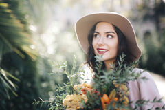 Fine art lifestyle Fashion model flowers in park. Woman in stylish hat coat and dress in park Rome Italy Royalty Free Stock Photo