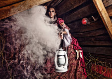 Fine art photo of a young fashion lady in a dark mystic location. Royalty Free Stock Images