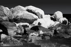 Snowy and icy rocks in the ocean. Black and white Stock Photos