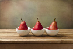 Fine art still life with red pears. On wooden table Royalty Free Stock Image