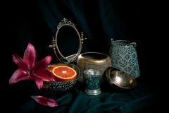 Fine art style low key still life with antique decor items on dark background. Composition of vases, flowers, mirror, orange with royalty free stock photography