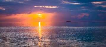 Fine art of sunset. A bright fantastic sunset in the tropics. The sun sets over the horizon of the ocean.  Image is an abstract illustration or painting, fine Royalty Free Stock Photo