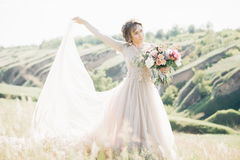Fine art wedding photography. Beautiful bride with bouquet and dress with train in nature. Fine art wedding photography. Beautiful bride with bouquet and dress Stock Photo