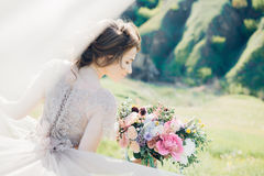 Fine art wedding photography. Beautiful bride with bouquet and dress with train in nature Stock Photography