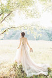 Fine art wedding photography. Beautiful bride with shoes and dress with train against the sunin nature Royalty Free Stock Photos