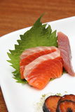 Fine Asian Finger Food. Raw fish slices served on white plate, placed on brown table Stock Photos