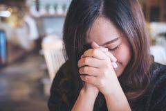 Fine asiatica della donna lei occhi al pregare ed al desiderio per una buona fortuna Fotografie Stock Libere da Diritti