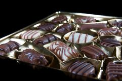 Fine assorted brown white chocolate pralines on golden package stock photography