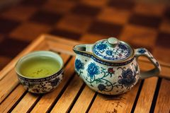 Fine ceramic small blue chinese teapot with a small tasting cup full of oolong tea stock images