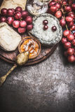 Fine cheese variety with wine, grapes and honey sauces on vintage background, top view, border Stock Photo