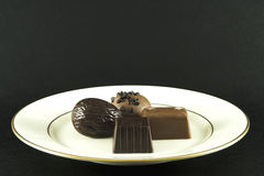 Fine China and Chocolate. An expensive plate of chocolate. Isolated on matte black background Stock Photos