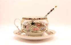Fine China cup with saucer and spoon. Over a white background Royalty Free Stock Images