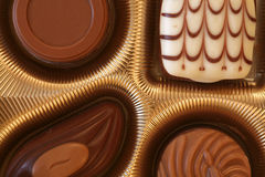 Fine chocolate. Fine selection of chocolates in a golden box, close up Royalty Free Stock Images