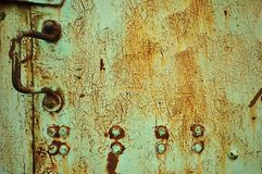 Fine Cracks. A faded green metal door covered in small fine cracks all over causing the metal to oxidize and a rusty color to appear. Metal handle with two rows Royalty Free Stock Photo