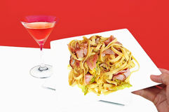 Fine cuisine. Meal dining fettucini italian cuisine pasta , red  and white table setting with glass of wine Stock Photography