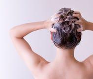 Fine dei capelli degli sciampi della donna su con entrambe le mani su un fondo bianco Fotografia Stock