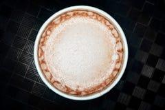 Fine della bevanda del cacao della cioccolata calda su macro struttura della schiuma su fondo scuro fotografia stock libera da diritti