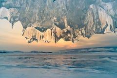 Fine della caverna di ghiaccio su nel lago dell'acqua di Baikal con il fondo del cielo di tramonto Fotografia Stock Libera da Diritti