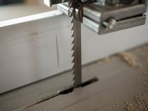 Fine della lama della sega a nastro sul colpo, sulla polvere di legno e sui chip fotografie stock
