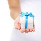 Fine della mano del contenitore di regalo/regalo di natale o del presente su Immagini Stock