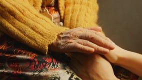 Fine della pelle della grinza della mano della tenuta della giovane donna della donna anziana su archivi video