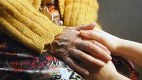 Fine della pelle della grinza della mano della tenuta della ragazza della donna anziana su Immagini Stock Libere da Diritti