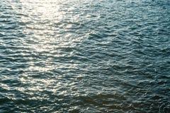Fine della superficie dell'acqua di mare su con la luce scintillante del sole nella sera Immagini Stock Libere da Diritti