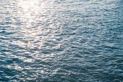 Fine della superficie dell'acqua di mare su con la luce scintillante del sole nella sera Fotografia Stock
