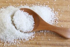 Fine Desiccated Coconut. The close up shot of some fine desiccated coconut on the wooden cutting board Royalty Free Stock Photography