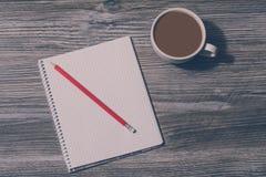 Fine di cui sopra superiore sulla foto del caffè fresco caldo saporito di mattina con latte ed il blocco note con la matita rossa Fotografie Stock Libere da Diritti