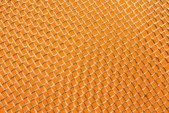 Fine di griglia del metallo su su un fondo arancio Fotografia Stock Libera da Diritti