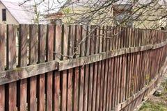 Fine di legno del recinto su Vecchia rete fissa immagine stock