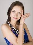 Fine di riserva della foto sul ritratto di bello giovane modello femminile che posa contro il fondo grigio fotografia stock