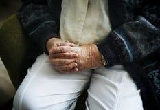 Fine di seduta dell'uomo senior su sul suo tenersi per mano Immagini Stock