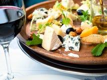 Fine di vetro dell'aperitivo del piatto di formaggio e del vino rosso su immagini stock