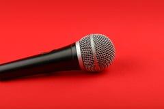 Fine di vista laterale del microfono su su rosso Fotografie Stock Libere da Diritti